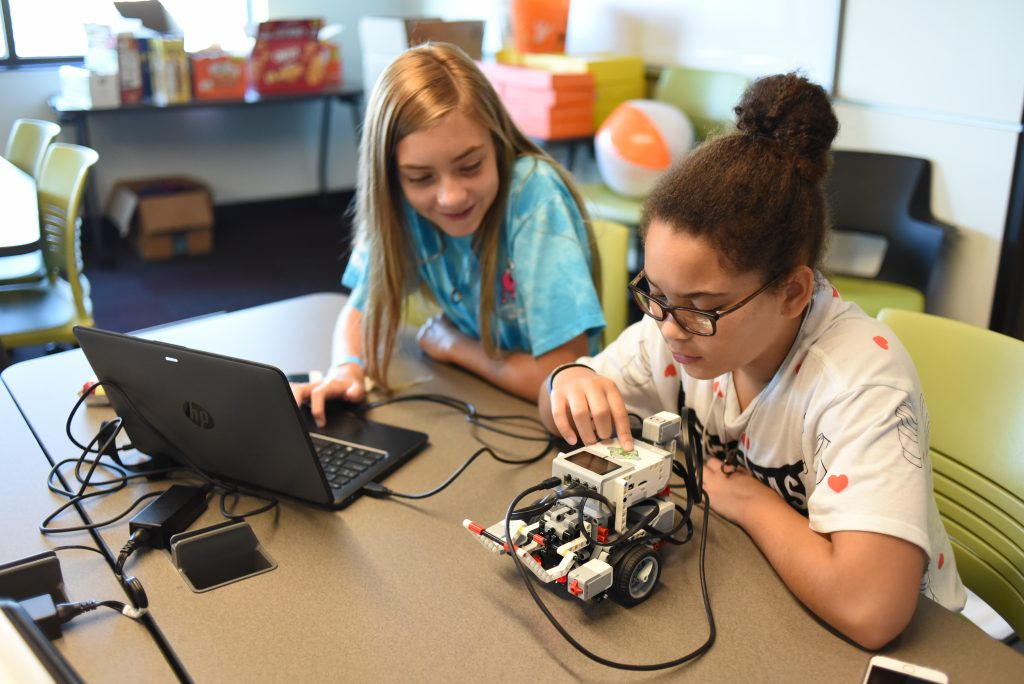 Destiny Sommer and Lydia Nystrom work with their robot